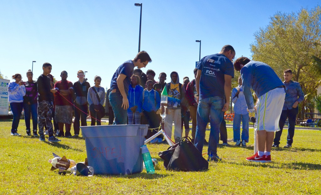 Students from North Miami Middle School perform in a bottle rocket experiment with FIU's SHPE