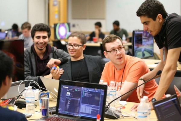 MangoHacks mentor Jacob Jenkins (center, orange shirt) brainstorms with attendees Baruch Hen (left) and FIU students Jose Morgan (center, dark jacket) and Lukas Borges (right, standing).