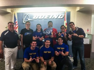 "The students celebrated their first-place victory, making ""w"" signs for ""win."" From Left to right, top row: Boeing engineers Scott Southwell and Amy Ebert, with students Alexsandra Olaya, Jorge Cisternas, Stephanie Forero, Jose Medina. Left to right, bottom row: students Edwin Moore III, David Guerrero and Julian Rozo"
