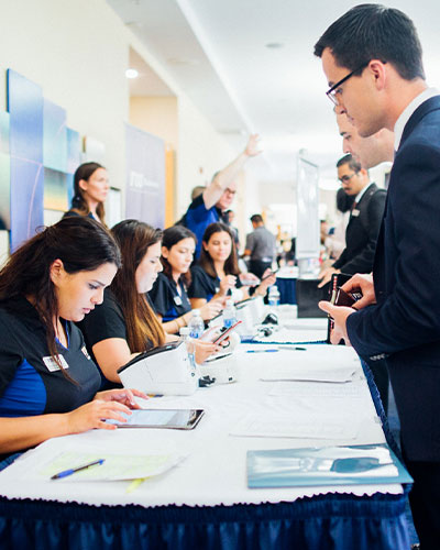 Professionally dressed students checking in at an event
